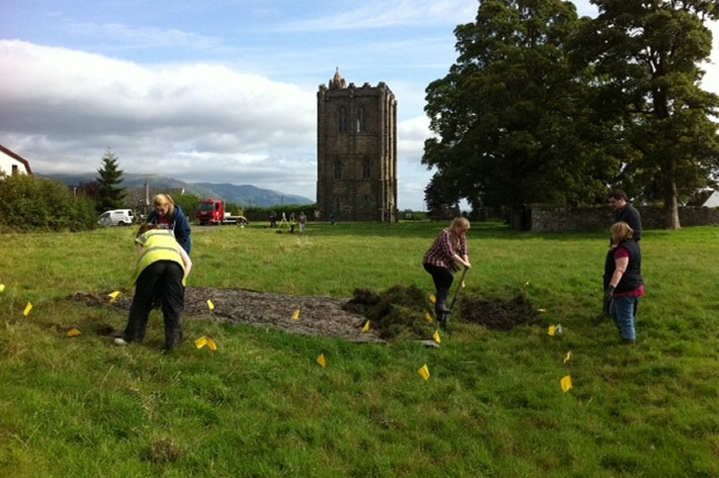 Volunteers breaking ground in the shadow of the abbey tower.